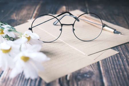 papers , flower, eyeglass and a fountain pen on wooden table Standard-Bild