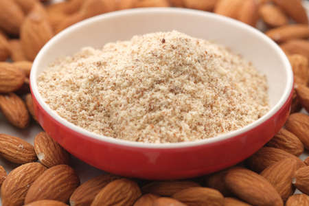 almond powder in a container with almond nut on table Standard-Bild