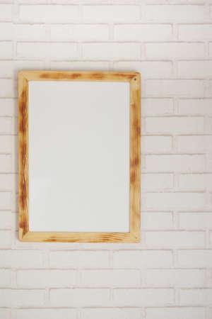 Black frame mockup on table against white wall,