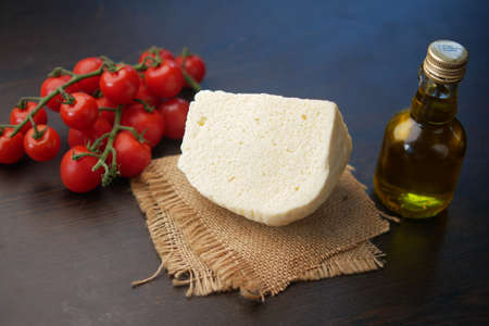 cherry tomato, cheese and olive oil on table