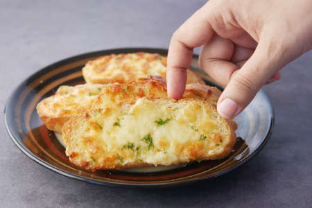 hand pick a garlic bread on a plate