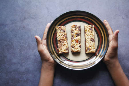 child boy hand hold a plate of Almond , chocolate and oat protein bars Standard-Bild