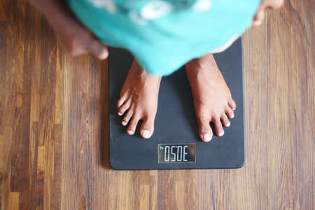young mans feet on weight scale top view