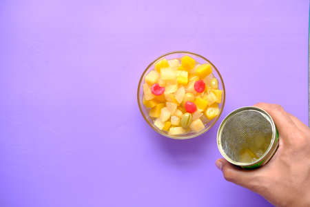 Open can of fruit cocktail on table ,