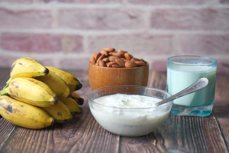 fresh yogurt in a bowl with almond nut, banana and milk on table ab