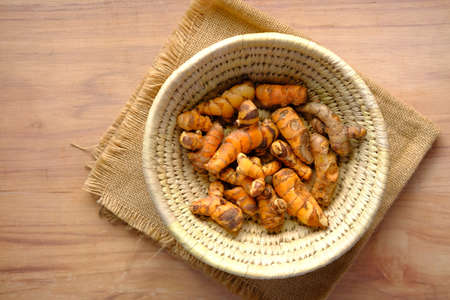 top view of turmeric root in bowl on table ,