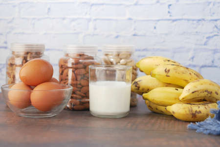 eggs in a plastic container, milk and almond nut in table