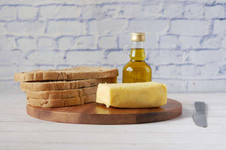slice of butter and whole meal bread on chopping board Standard-Bild