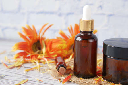 eucalyptus essential oils in a glass bottle and flower on table