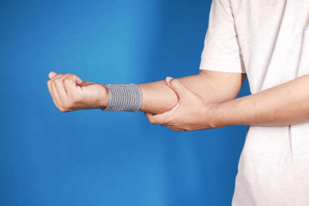hand with wrist support against blue background.