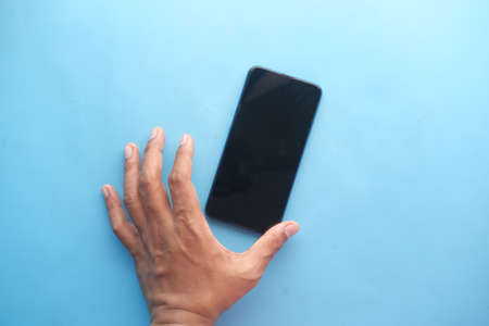 Close up of young man hand holding a smart phone on blue Standard-Bild