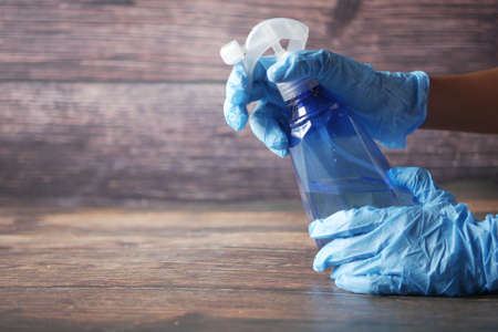hand in blue rubber gloves holding spray bottle with copy space Standard-Bild