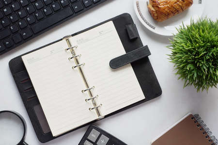 high angle view of open notepad and office stationary on white Standard-Bild