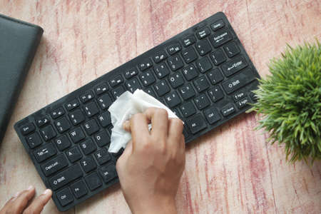 close up of person hand cleaning keyboard with cloth Standard-Bild