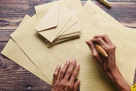 senior women hand writing on old paper with fountain pen