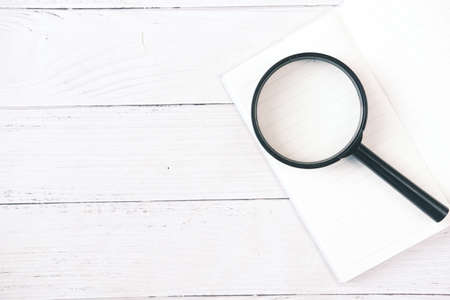 open book and magnifying glass on table. Standard-Bild