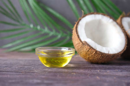 slice of fresh coconut and bottle of oil on a table