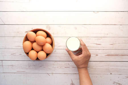 eggs in a bow and a glass of milk on table Standard-Bild