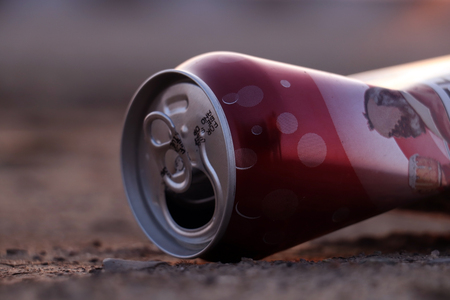 crumpled empty beer can on the ground Stock Photo