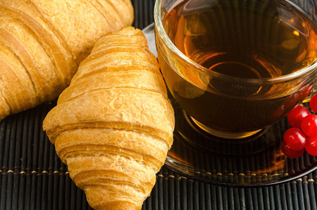 tea hot drink: fresh cup of hot black tea with croissants, invigorating drink