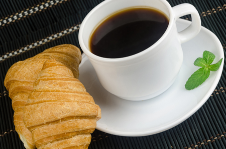 invigorating: fresh cup of hot black coffee with croissants, invigorating drink