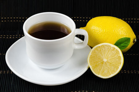 cup of fresh tea with lemon on rustic wood background, breakfast concept Stock Photo