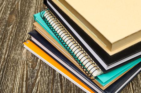 folded stack of workbooks. On wooden background