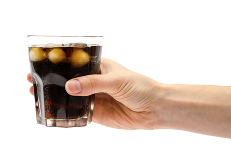 hand of girl holding glass of rum with coke. Isolated on white background