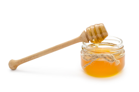 jar with honey and honey spoon on it. Isolated on white background