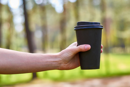the girls hand reaches for a Cup of morning coffee