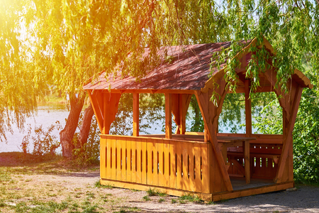 gazebo for family entertainment and is made of wood, stands on the shore of the lake in the sun Stock Photo