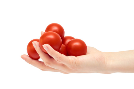 Beautiful female hand holds red tomato gesture. Isolated on white background. Stock Photo