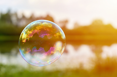 Soap bubbles on the banks of the River Fly downwind. The concept of lightness and airiness, sunlight.