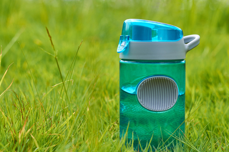 Sport plastic bottle stands in a field on a green grass.