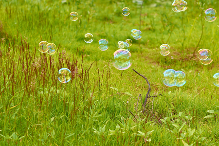 airiness: Soap bubbles on a green field fly downwind. The concept of lightness and airiness. Stock Photo