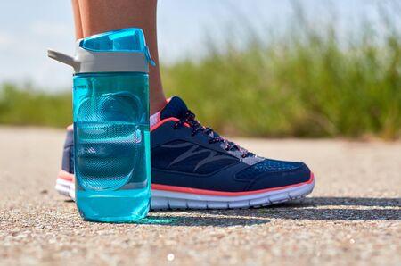 Beine des Mädchens in Turnschuhen. Sportflasche mit Wasser. Standard-Bild - 84435288
