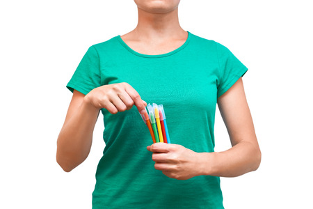 girl holding colored felt pens in her hand. Isolated on white background. Stock Photo