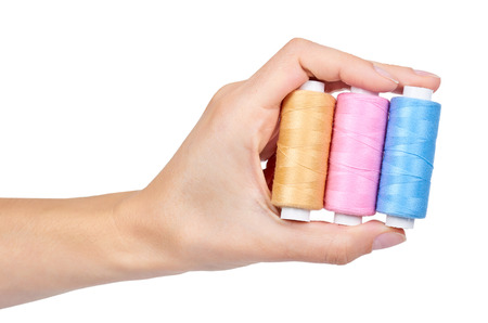 spool of thread in hand isolated on white background. Stock Photo