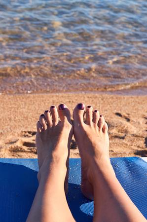 Beautiful woman's legs on the beach sand.