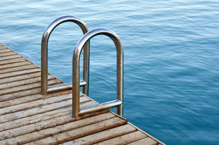 Swimming pool with metal stair. Blue water.