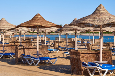 sunbeds and umbrellas, sea vacation concept idea. Stock Photo
