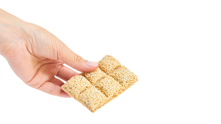 sesame brittle brick in hand Isolated on white background. Imagens
