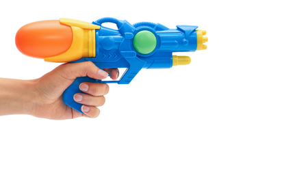 Female hand holds blue squirt gun. Isolated on white background. copy space, template.