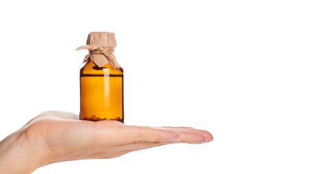 bottle with tincture in hand isolated on white background. copy space, template.