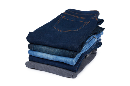 Foldet jeans in pile, isolated on white background.