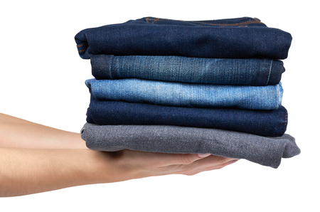 Foldet jeans in pile with hand, isolated on white background. Stock Photo