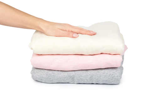 Pile of foldet cloth with hand, isolated on white background.