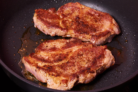 grilled meat steak with spices on fying pan.