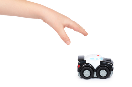 Black toy police car with kid hand, isolated on white background.