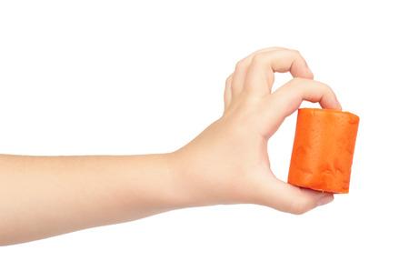 Orange plasticine bar with kid hand, isolated on white background.